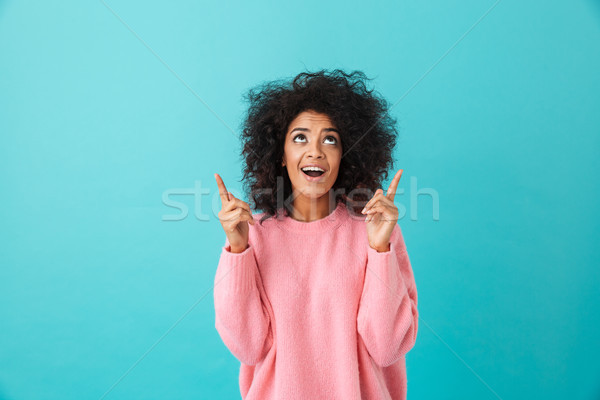 Cheerful american woman in colorful shirt looking upward and poi Stock photo © deandrobot