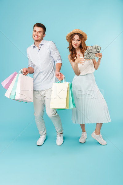 Emotional happy caucasian loving couple holding money and shopping bags. Stock photo © deandrobot