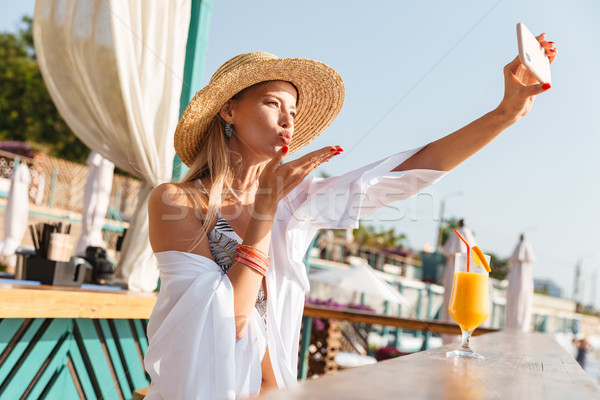 Photo of stunning blond woman 20s in straw hat smiling and takin Stock photo © deandrobot