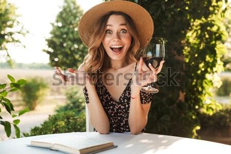 Młoda kobieta posiedzenia Kafejka parku obraz śmiechem Zdjęcia stock © deandrobot