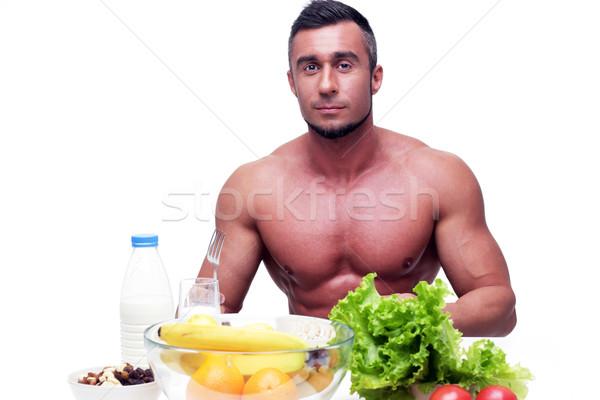 Przystojny muskularny człowiek posiedzenia tabeli zdrowa żywność Zdjęcia stock © deandrobot