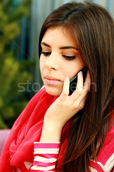 Young pensive woman talking on the phone Stock photo © deandrobot