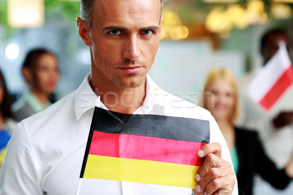 Handsome businessman holding flag of Germany in front of colleagues Stock photo © deandrobot
