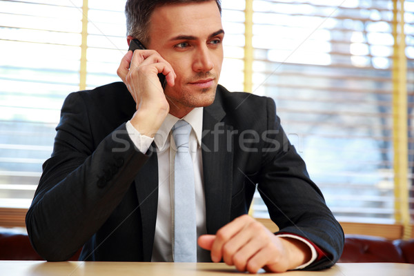 Confident businessman sitting and talking on the phone at office Stock photo © deandrobot