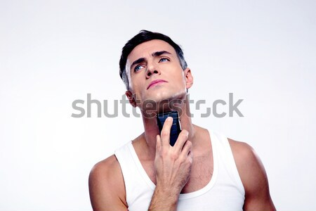 Confident man shaving with electric razor over gray background Stock photo © deandrobot