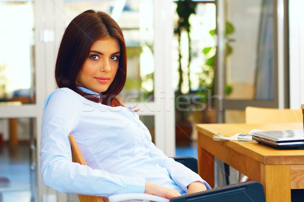 Happy young woman sitting in the office Stock photo © deandrobot