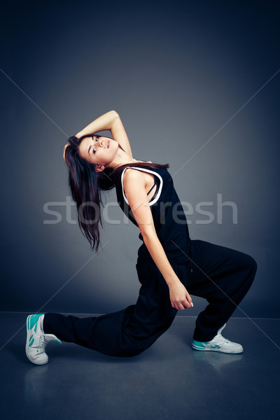 Young beautiful dancing woman in black hip-hop suit on dark background Stock photo © deandrobot