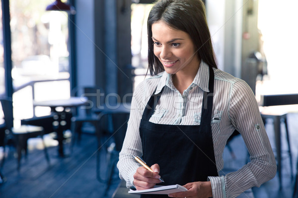Smiling beautiful female waiter in apron Stock photo © deandrobot