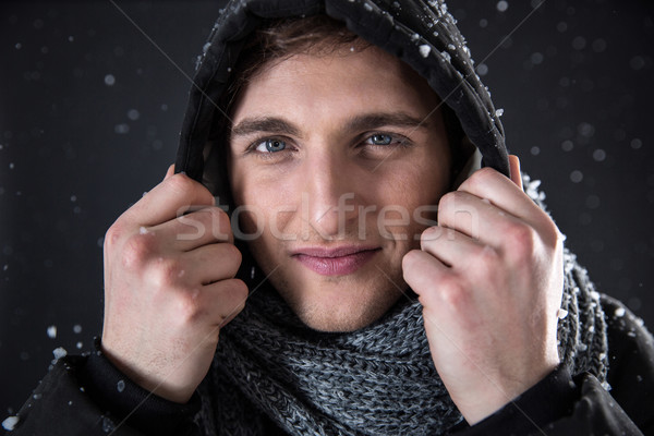 Portrait of a happy man in winter cloth with snow on background Stock photo © deandrobot