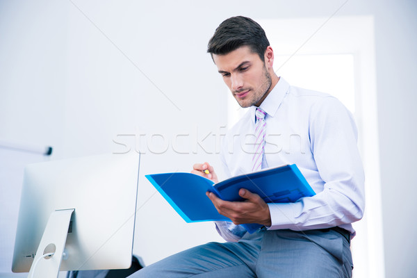 Businessman sitting on the table and reading document Stock photo © deandrobot