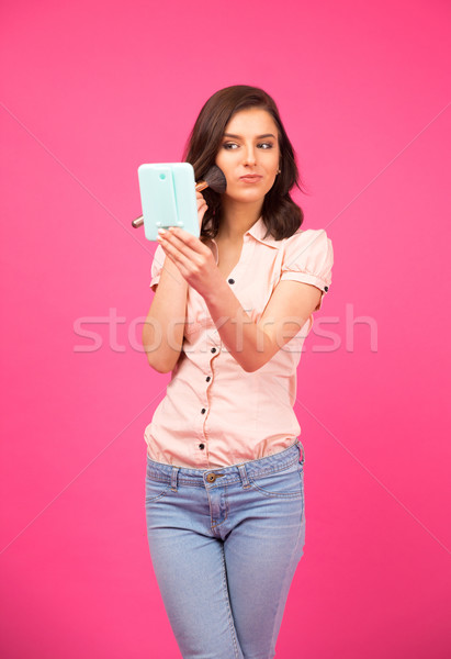 Attractive young woman making makeup Stock photo © deandrobot