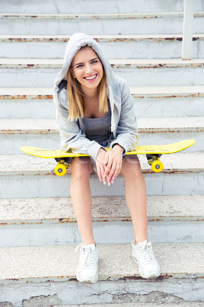 girl sitting on the stairs with skateboard Stock photo © deandrobot