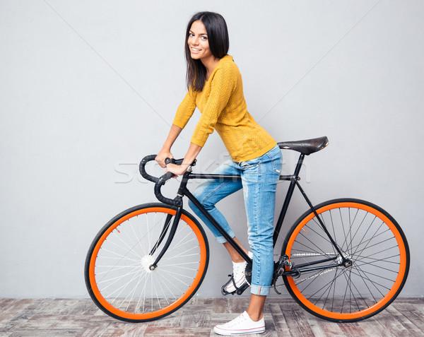 улыбающаяся женщина велосипед портрет серый глядя Сток-фото © deandrobot