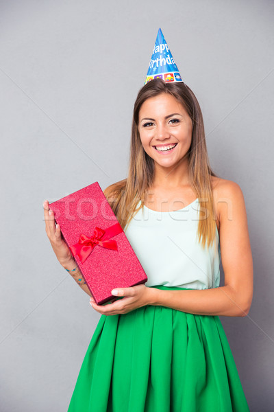 Stock photo: Cute girl in party hat holding gift box