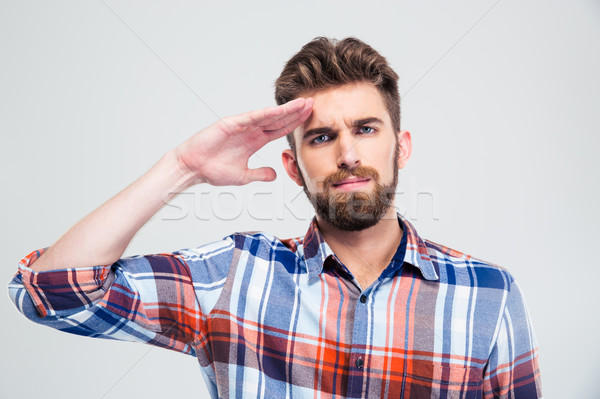 Portrait of a young man saluting Stock photo © deandrobot