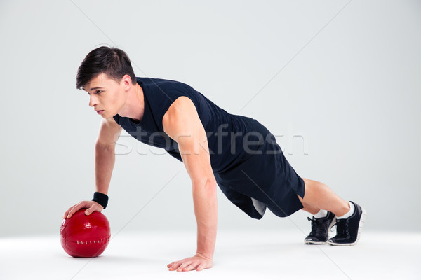 Sportsman man workout with fitness ball Stock photo © deandrobot