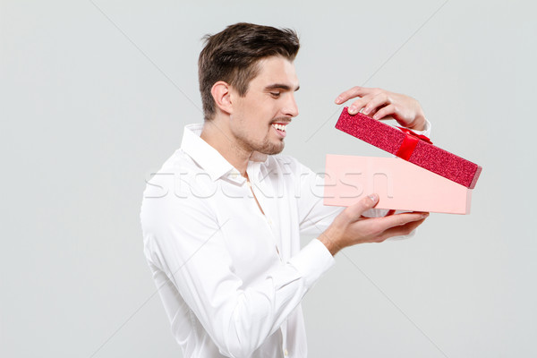 Happy young guy looking in pink box Stock photo © deandrobot