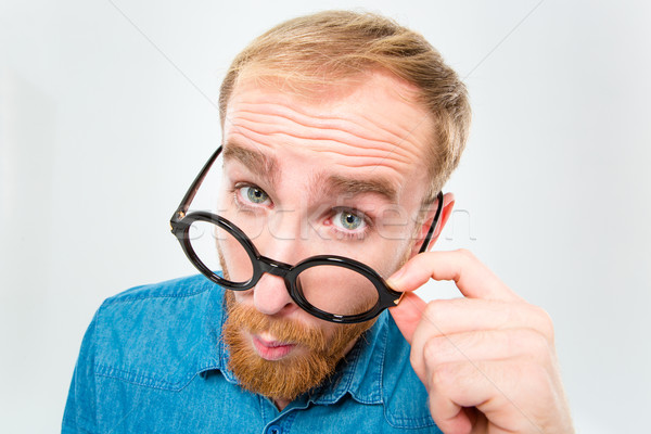 Amusing young man with beard looking over black round glasses Stock photo © deandrobot