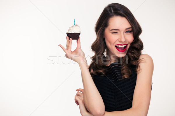 Retro styled woman holding birthday cupcake with candle and winking Stock photo © deandrobot