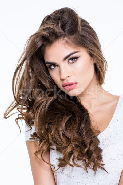Charming woman with long curly hair looking at camera Stock photo © deandrobot