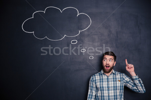 Inspired man pointing up and having an idea over blackboard  Stock photo © deandrobot