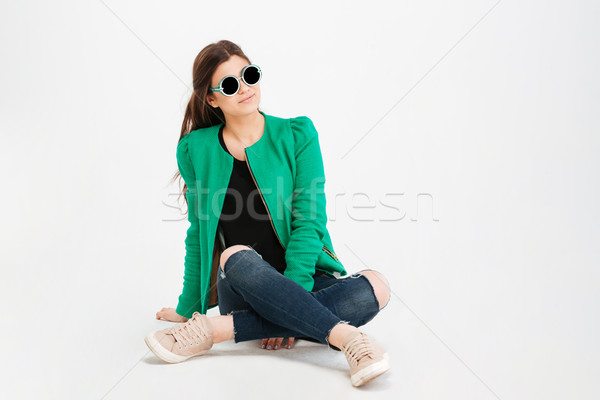 Smiling woman in green jacket, ripped jeans and sunglasses  Stock photo © deandrobot