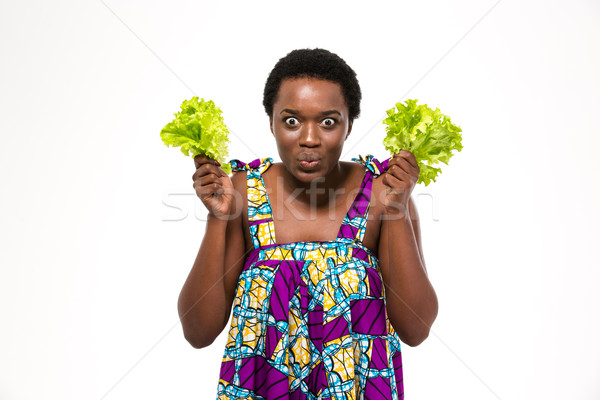 Funny  african woman in colorful sundress holding leaves of lettuce Stock photo © deandrobot