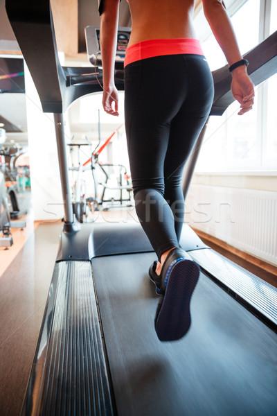 Attractive sportswoman running on treadmill in gym Stock photo © deandrobot