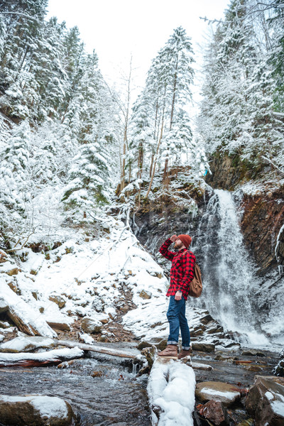 Attractive bearded young man walking near mountain waterfall in winter Stock photo © deandrobot