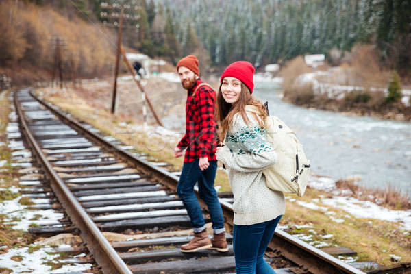 Happy young couple walking along railroad Stock photo © deandrobot