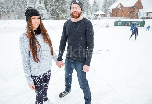 Beautiful couple in ice skates having fun  Stock photo © deandrobot