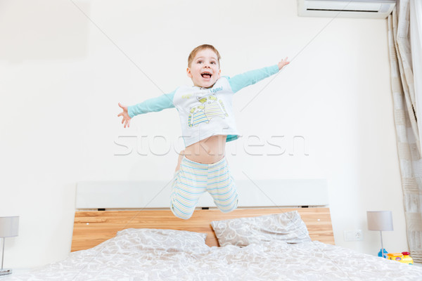 Happy little boy jumping on bed Stock photo © deandrobot