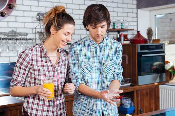 Stock photo: Beautiful couple drinking juice and cooking using flour on kitchen