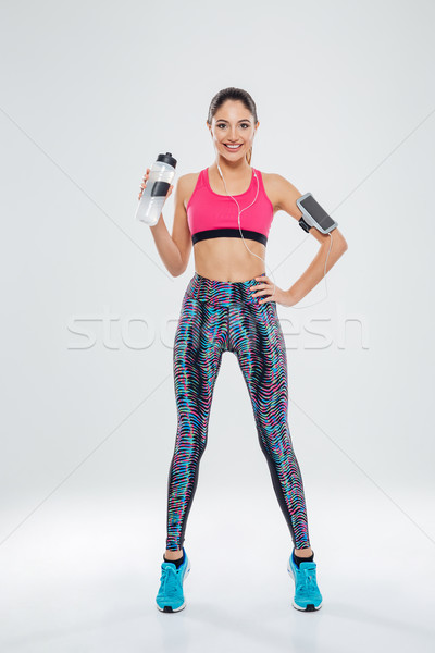 Happy sports woman holding shaker with water Stock photo © deandrobot