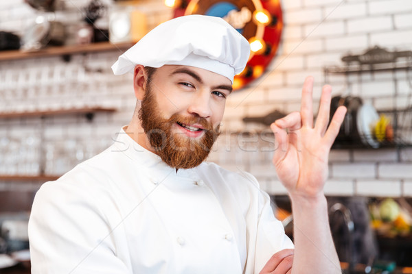 Cheerful chef cook showing ok sign on the kitchen Stock photo © deandrobot