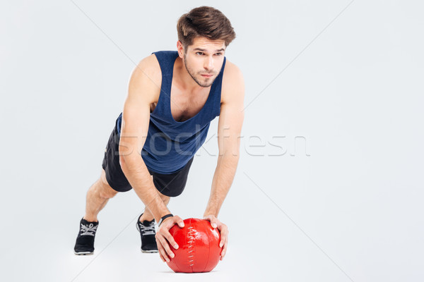 Handsome young man athlete doing push ups on red ball Stock photo © deandrobot
