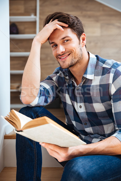 Close up portrait of a young handsome man reading book Stock photo © deandrobot