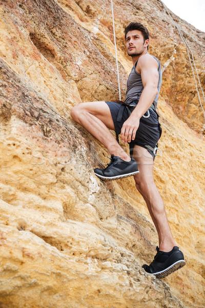 Młody człowiek wspinaczki stromy ściany górskich młodych Zdjęcia stock © deandrobot