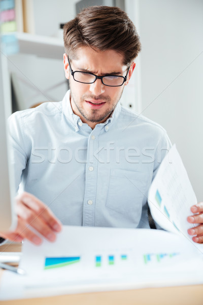 Businessman sitting on the table and reading document in office Stock photo © deandrobot