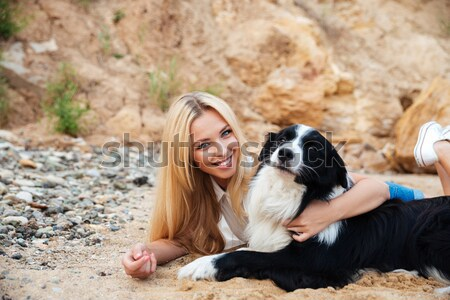 Happy woman relaxing with dog on the beach Stock photo © deandrobot