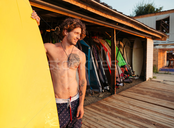 Surfer getting surf board ready to catch waves Stock photo © deandrobot