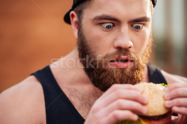Amazed shocked young man holding and looking at hamburger outdoors Stock photo © deandrobot