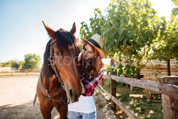 Redhead woman cowgirl taking care of her horse on farm Stock photo © deandrobot