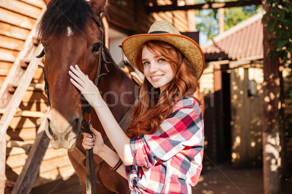 Happy woman cowgirl with her horse in village Stock photo © deandrobot