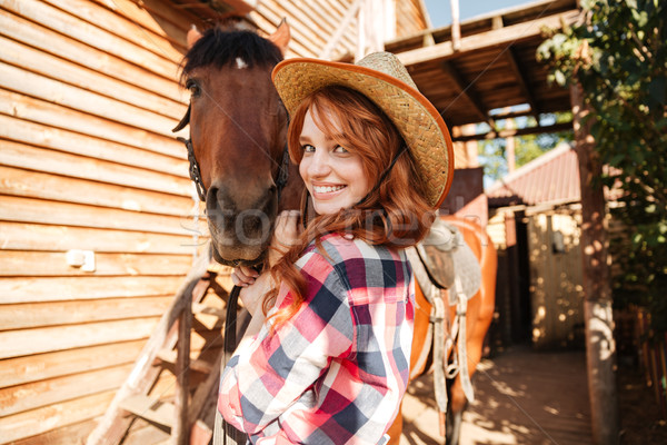 Cheerful cute young woman cowgirl in hat with horse Stock photo © deandrobot