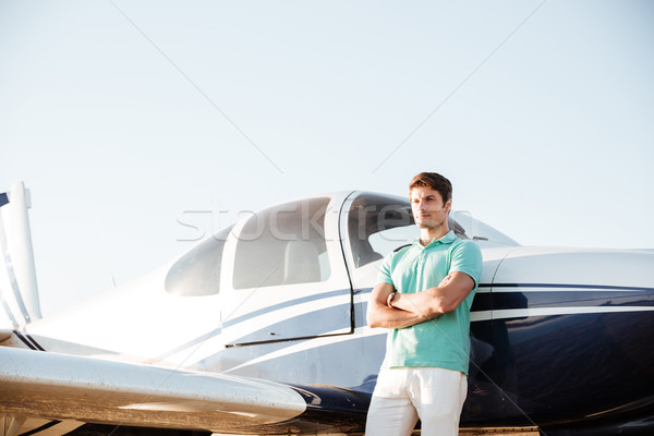 Confident young man standing in front of small airplane Stock photo © deandrobot