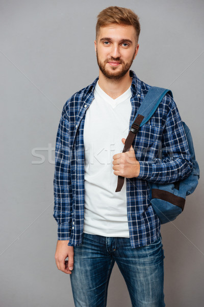 Smiling casual man with backpack looking at camera Stock photo © deandrobot