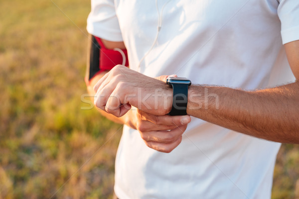 Close up of sports male hands with smartwatch Stock photo © deandrobot
