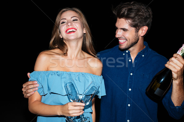 Joyful couple holding glasses and bottle of champagne at night Stock photo © deandrobot