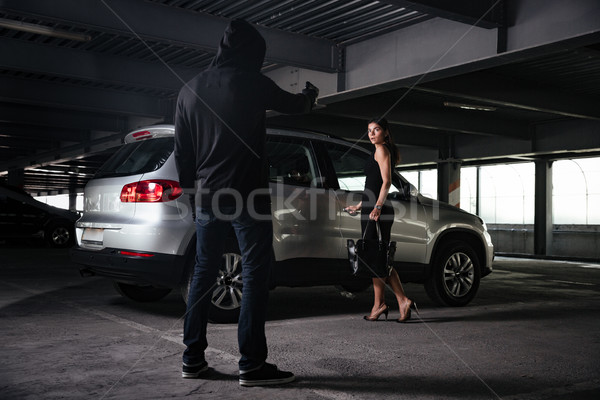 Man thief standing and threatening with gun to young woman Stock photo © deandrobot